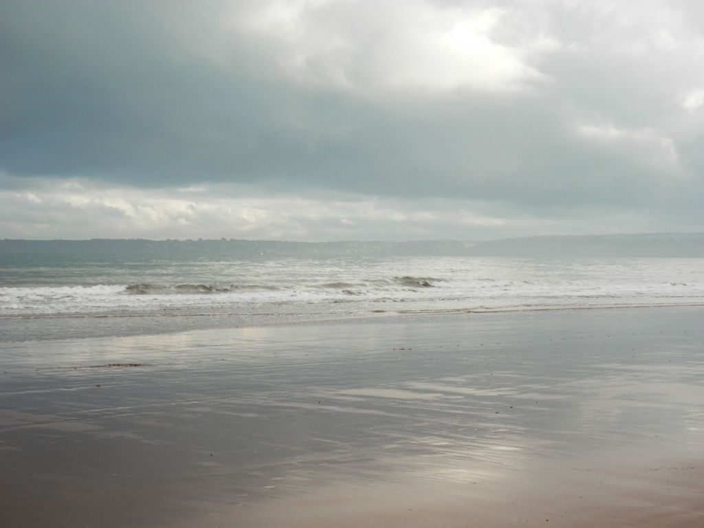 Grey clouds on wet sand